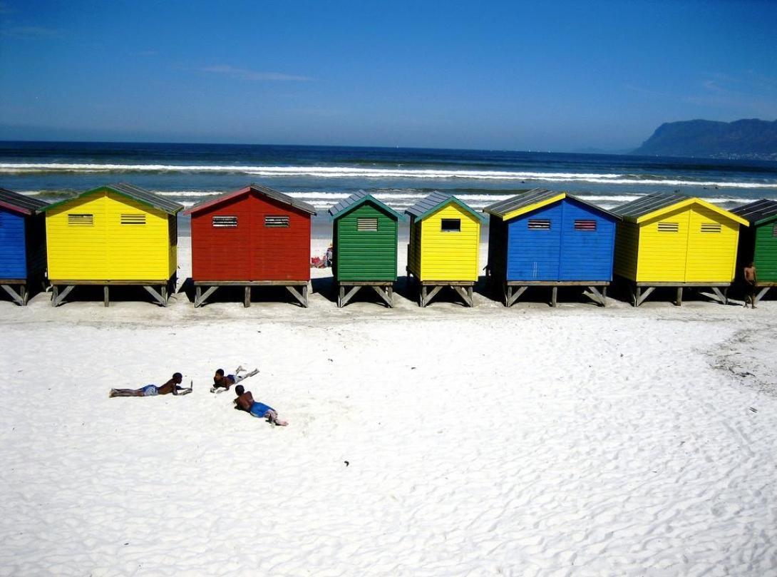 Tre barn solar i den vita stranden i Muizenberg i Sydafrika, där volontärer kan arbeta med att lära barn att surfa.